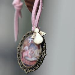 """Medalla bronce ovalada con cristal lupa 2x3 cm. Imagen """"Angelito cuna""""."""