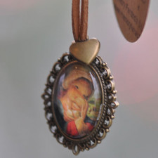 """Medalla bronce ovalada  con cristal lupa 2x3 cm. Imagen """"Virgen ventana"""". Cinta de ante camel y mini corazón dorado."""