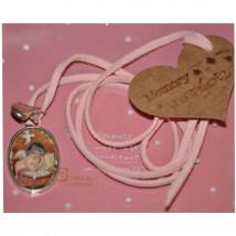 """Medalla plateada ovalada 2x3 cm con cristal lupa. Imagen """"Angelito cuna""""."""