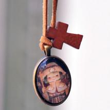 """Medalla plateada ovalada  con cristal lupa 2x3 cm. Imagen """"Apóstol Santiago"""". Cinta de ante camel y mini cruz de madera."""