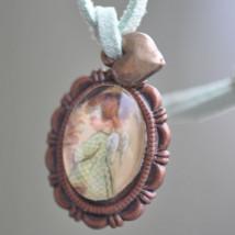 "Medallita bronce ovalada  con cristal lupa 13x18 mm. Imagen ""Angelito vichy""."